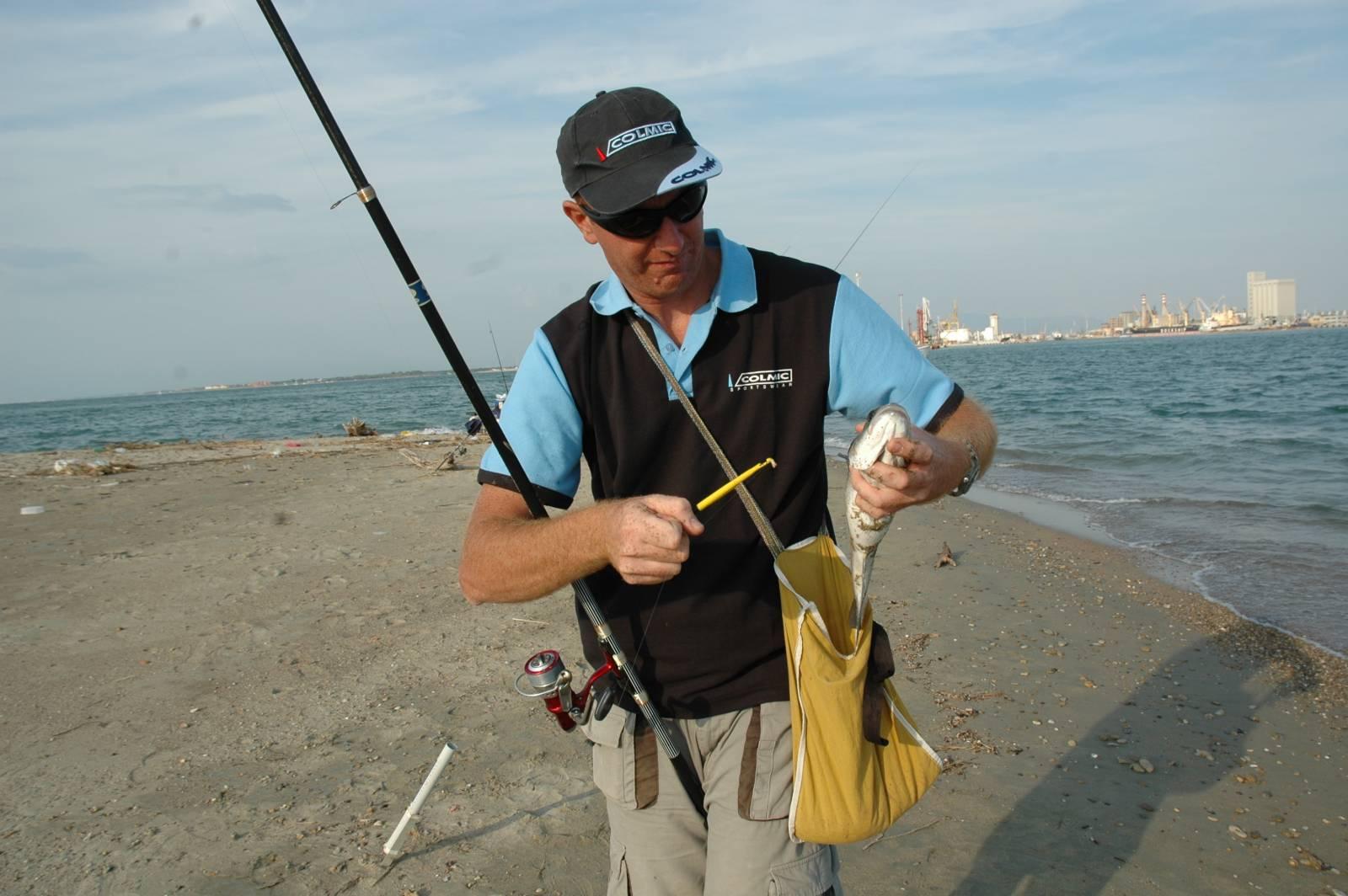 Una spigola catturata con il bigattino. Sullo sfondo possiamo intravedere il colore del mare leggermente torbido